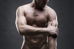 Dolore nel gomito Ente maschio muscolare Culturista bello che posa sul fondo grigio Fine scura sul colpo dello studio Immagini Stock