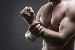 Dolore nella mano Ente maschio muscolare Culturista bello che posa sul fondo grigio Fine scura sul colpo dello studio Immagini Stock Libere da Diritti