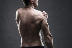 Dolore nella spalla Ente maschio muscolare Culturista bello che posa sul fondo grigio Fine scura sul colpo dello studio Immagini Stock