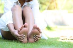 Dolore ritenente della giovane donna nel suo piede sull'erba, concetto di salute fotografia stock