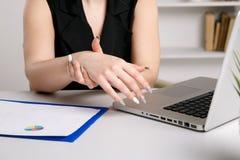 Dolore ritenente femminile in polso dopo avere lavorato al computer portatile immagini stock