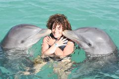 Dolphin Assisted Therapy in blue water. Dolphin Assisted Therapy for Happy child and dolphin in blue water stock photo