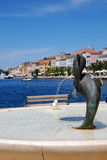 Dolphin fountain in Mali Losinj,Croatia. Seagull in dolphin fountain in Mali Losinj on the main square with the seaview and houses in background Royalty Free Stock Images