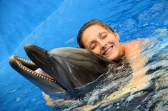 Dolphin love. Young girl with love and awing hugging a dolphin in the water Royalty Free Stock Photography