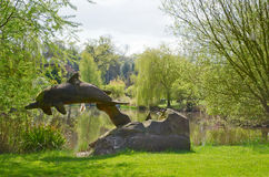 Dolphin sculpture in nature. A sculpture of a dolphin, beside a lake, on a sunny day Stock Image