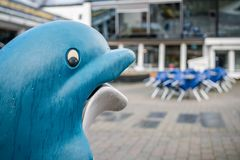 Dolphin shaped rubbish bin. Blue dolphin shaped rubbish bin outside restaurant in Norway Stock Photography