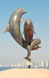 Dolphin statute on the Malecón in Puerto Vallarta. A statute of dolphins stands on the Malecón in Puerto Vallarta, Mexico, in front of the Pacific Ocean.  This Royalty Free Stock Photography