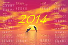 Dolphins 2014 calendar - 3D render. 2014 monthly calendar and shadow of two small dolphins jumping upon ocean toward the sun by red sunset in background Stock Photo