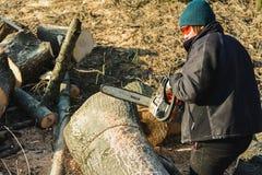 Dolyna, Ukraine, am 25. Februar 2019 Eine Frau schnitzt ein Gras, das Meißel Baum von Stihl für das Ernten des Brennholzes im Win lizenzfreie stockfotografie