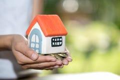 Domów modele i moneta w istot ludzkich rękach, Hipoteczny pojęcie pieniądze domem od monet zdjęcia stock