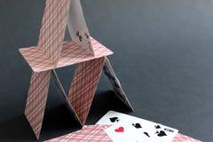 Dom budował od kart do gry na czarnym tle zdjęcia stock