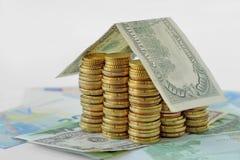 Dom budujący z monetami i dolarowym banknotem obrazy stock