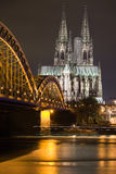 Dom in Cologne at night lighting. Dom in Cologne with arcs of Hohenzollern bridge with reflection in Rhine river Royalty Free Stock Image