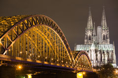 Dom in Cologne at night lighting. Dom in Cologne with arcs of Hohenzollern bridge Stock Photo