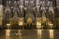 Dom in Cologne at night lighting. Night lighting of main portal of Dom in Cologne with walking people Stock Photo