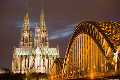 Dom in Cologne at sunset. Dom in Cologne with arcs of Hohenzollern bridge at sunset lighting Stock Photography
