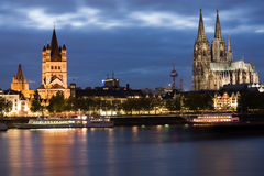 Dom in Cologne at sunset. Dom and Great St. Martin church in Cologne at sunset lighting with reflection in river Rhine Royalty Free Stock Image