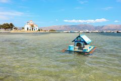 Dom dla kaczek na wodzie w Elafonisos wiosce na tle ażio Spyridon kościół i malowniczy seascape Elafon Fotografia Royalty Free