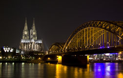 Dom and Hohenzollern bridge in Cologne. At night lighting with reflection in river Rhine Stock Images