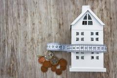 Dom kosztuje pojęcie Dom, pieniądze monety i pomiarowa taśma na drewnianym tle, Utrzymanie koszty Zapłata dla rachunek za usługę  obraz royalty free