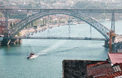 Dom Luis bridge and a ship in Porto on a sunny day. PORTO, PORTUGAL - JUNE 18 2015: Famous Eiffel arch bridge Dom Luis in Porto on a sunny day with a ship moving Stock Photography
