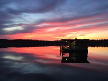 Dom na Jeziornym zmierzchu odbiciu w wodzie fotografia stock