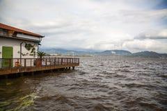 Dom na jeziorze, kłopot nawadnia i wiatr Zdjęcia Stock