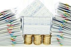 Dom na stosie złociste monety między podwójnym palowym przeciążeniem Fotografia Stock