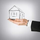 Dom na wirtualnym ekranie w mężczyzna ręce Zdjęcie Stock