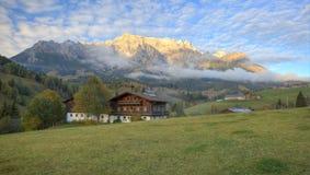 Dom na wsi przy pogórzami skalisty pasmo górskie zaświecali up złotym światłem słonecznym przy zmierzchem Zdjęcie Royalty Free