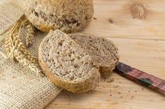 Dom piec brown chleba plasterki na drewnianym stole Zdjęcia Royalty Free