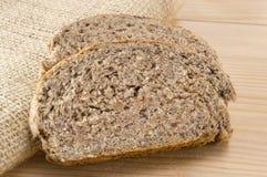 Dom piec brown chleba plasterki na drewnianym stole Zdjęcie Stock
