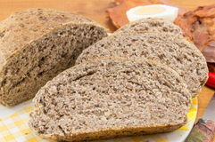 Dom piec brown chleba plasterki na stole Zdjęcie Stock