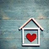 Dom robić kreda z czerwonym sercem w nim na błękitnym drewnianym backgrou fotografia royalty free