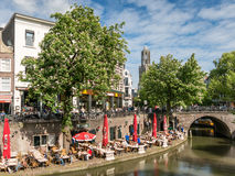 Dom Tower and Oudegracht canal in Utrecht, Netherlands. Dom Tower and people on outdoor terrace of restaurant alongside Oudegracht canal in the city of Utrecht Royalty Free Stock Photos