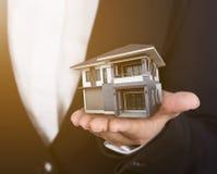 Dom w biznesowej ręce z światłem słonecznym Obraz Royalty Free