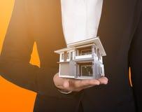 Dom w biznesowej ręce z światłem słonecznym Obrazy Stock