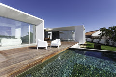 Dom z ogrodowym pływackim basenem i drewnianym pokładem Fotografia Royalty Free