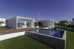 Dom z ogrodowym pływackim basenem i drewnianym pokładem Zdjęcia Royalty Free