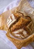 Dom zrobił Kwaśny rzemieślnik Literującemu ciasto chlebowi po piec w holenderskim piekarniku na marmurowym tle zdjęcie stock