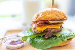 Dom zrobił stylowemu hamburgerowi z wielo- warstwami wołowina, ser i bekon, zdjęcie royalty free