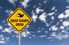 Cheap flights ahead. Illustrated in black text graphics with silhouette of bird on yellow highway sign against blue skies vector illustration