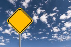 Yellow roadway sign. Blank yellow roadway caution sign against blue skies with copyspace stock photo