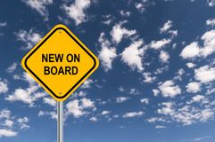 New On Board Sign. A yellow new on board sign surrounded by a blue sky with fluffy white clouds royalty free stock image