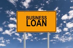 Business Loan street sign. Yellow rectangular street sign with BUSINESS LOAN written in black on it, against a blue sky and clouds background royalty free stock image