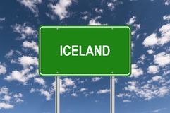 Iceland green highway sign. Green directional highway sign with white text graphics Iceland against blue skies with clouds stock image