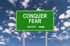 Conquer fear sign. Conquer fear road sign against blue sky royalty free stock photography