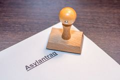 Domanda di asilo con il bollo di legno con la parola tedesca per l'applicazione di asilo fotografie stock