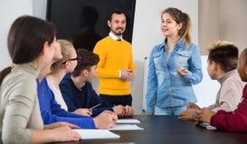 Domanda di risposta dei teacher's della studentessa allo scrittoio Immagini Stock