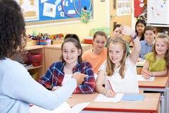 Domanda di risposta dell'allievo elementare femminile nella classe Immagini Stock Libere da Diritti